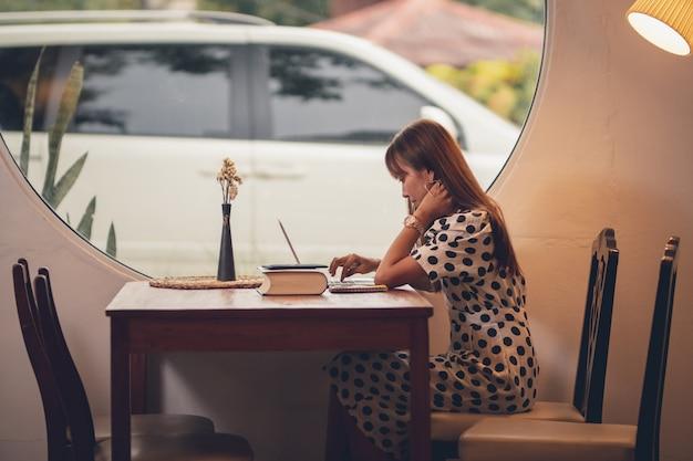 Femme d'asie à l'aide d'un ordinateur portable travaillant dans le temps libre avec heureux Photo Premium