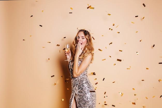 Femme Assez Mince Posant Sous Des Confettis Scintillants Sur Un Mur Lumineux Pendant La Fête Du Nouvel An Photo gratuit
