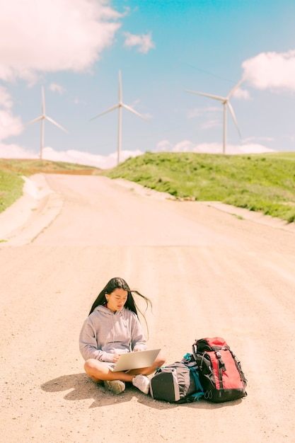 Femme assise au milieu de la route et travaillant sur un ordinateur portable Photo gratuit