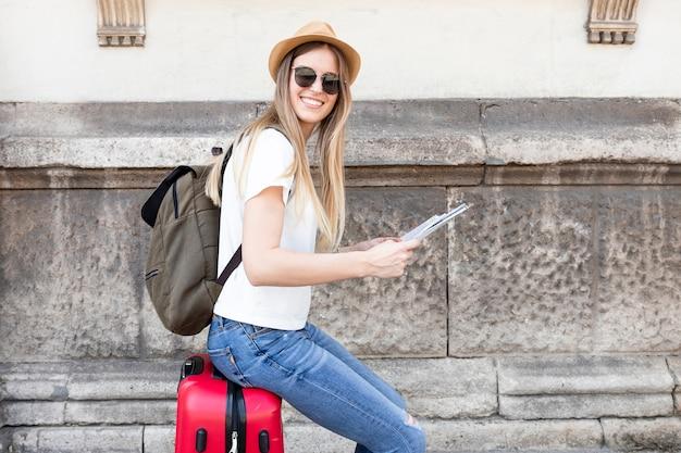 Femme assise sur un bagage sourit à la caméra Photo gratuit