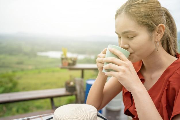 Femme assise sur un balcon avec vue naturelle et boire du café Photo Premium