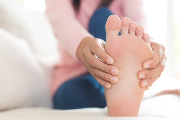 Femme assise et blessée au pied, sensation de douleur. concept de soins de santé. Photo Premium