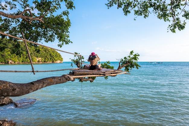 Une Femme Assise Sur Une Branche Sur Un Arbre En Mer à La Plage De Railay, Krabi, Thaïlande Photo Premium