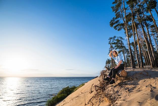 Femme assise sur une bûche et regardant à distance Photo gratuit