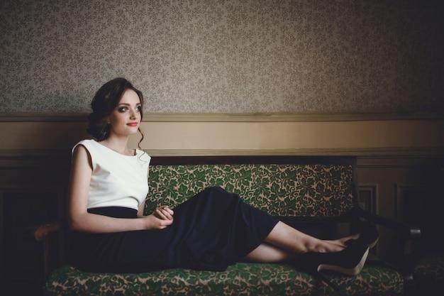 Femme assise sur un canapé antique Photo Premium