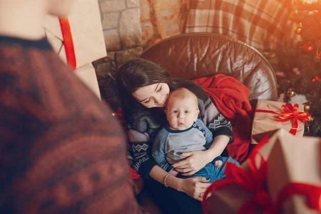Femme Assise Sur Un Canapé Avec Un Bébé Dans Ses Bras Et Avec Une Montagne De Cadeaux Marron Avec Noeud Rouge Photo gratuit