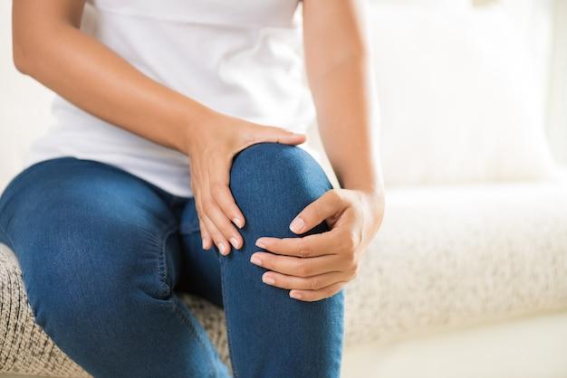 Femme assise sur un canapé et ressentant une douleur au genou. concept de soins de santé. Photo Premium