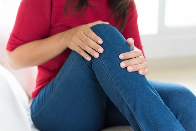 Femme assise sur le canapé et le sentiment de douleur au genou, soins de santé et concept médical. Photo Premium