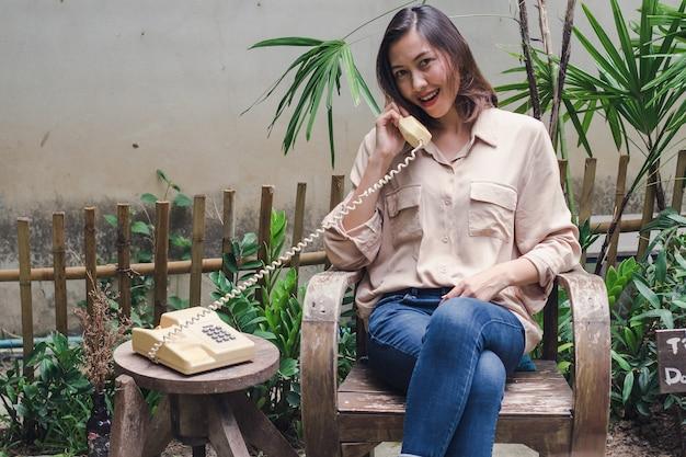 Femme assise sur une chaise en bois dans la cour Photo Premium