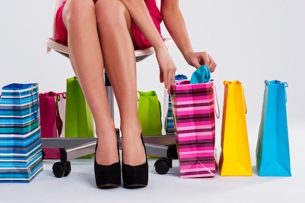 Femme Assise Sur Une Chaise à Côté De Sacs à Provisions Photo gratuit