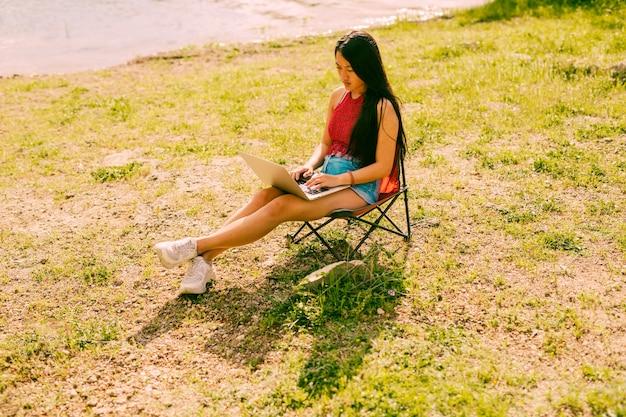 Femme assise sur une chaise à l'extérieur avec un ordinateur portable Photo gratuit