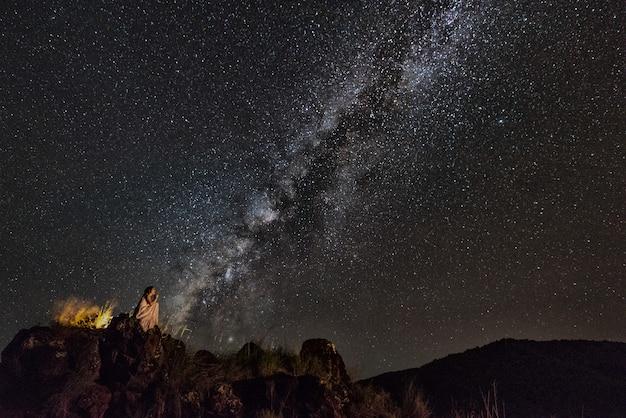 Femme assise sur la corniche en regardant les étoiles du ciel nocturne avec fond de voie lactée Photo Premium