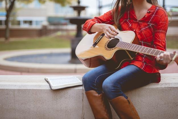 Femme Assise à Côté D'un Livre Tout En Jouant De La Guitare Avec Un Arrière-plan Flou Photo gratuit