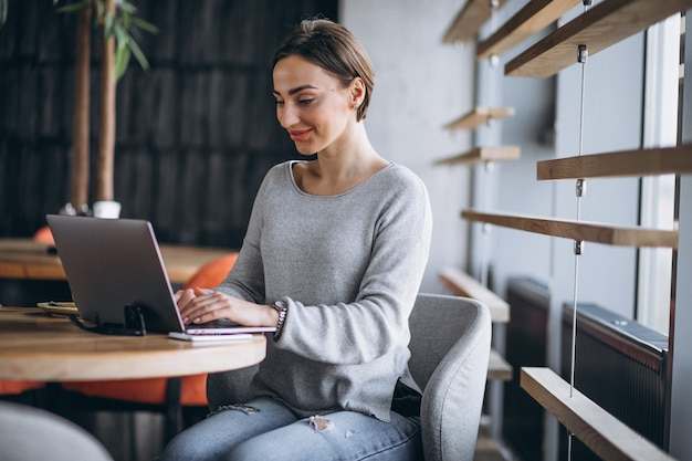 Femme assise dans un café, buvant du café et travaillant sur un ordinateur Photo gratuit