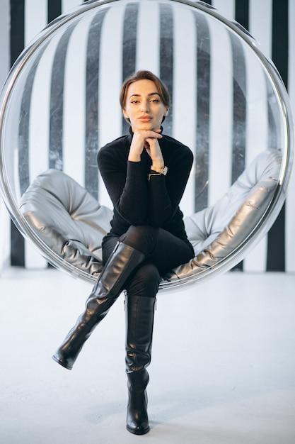 Femme assise dans une chaise en verre suspendue Photo gratuit