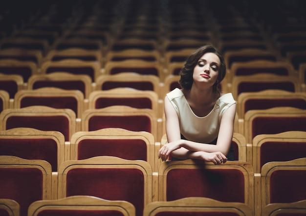 Femme assise dans les fauteuils d'un théâtre Photo Premium