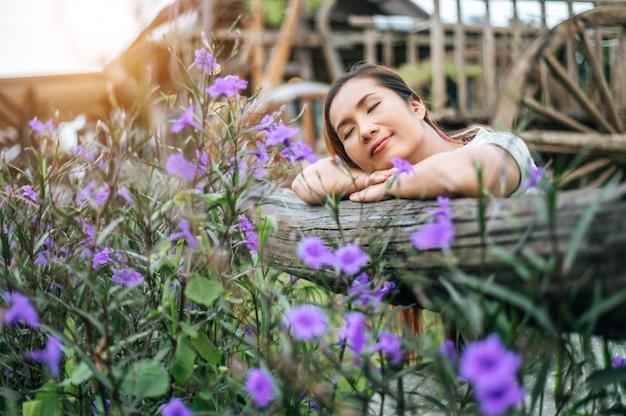 Femme assise dans le jardin de fleurs et posant ses mains vers la clôture en bois Photo gratuit