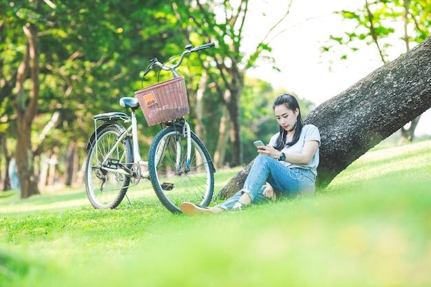 Femme assise dans un parc s'appuyant sur un arbre et écoutant de la musique sur des écouteurs avec un vélo Photo Premium