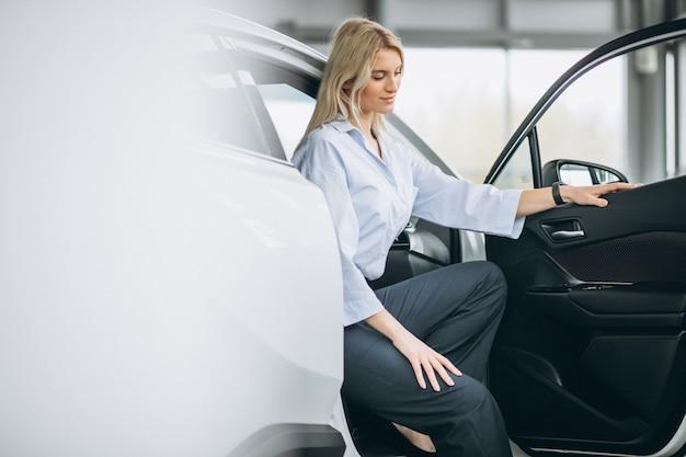 Femme assise dans une voiture dans une salle d'exposition Photo gratuit