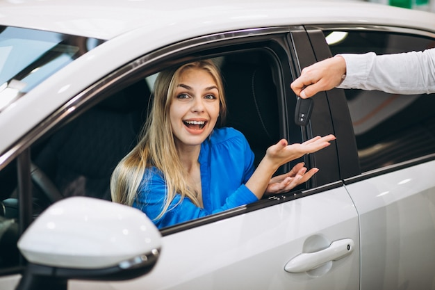 Femme assise dans une voiture et recevant les clés dans une salle d'exposition Photo gratuit