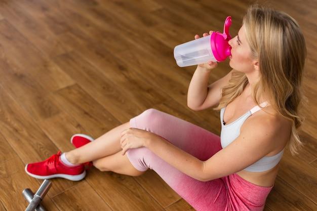 Femme assise et eau potable Photo gratuit