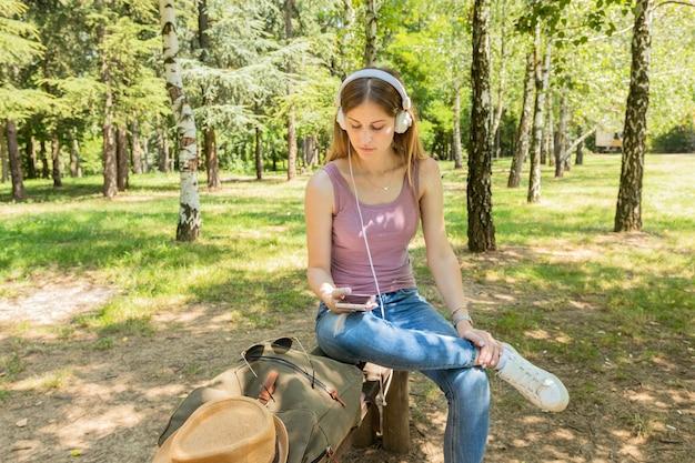 Femme assise et écoutant de la musique avec des écouteurs Photo gratuit