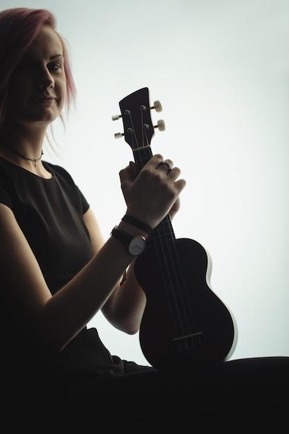Femme assise avec une guitare à l'école de musique Photo gratuit
