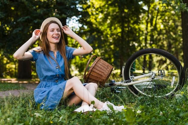 Femme assise sur l'herbe à côté du vélo Photo gratuit