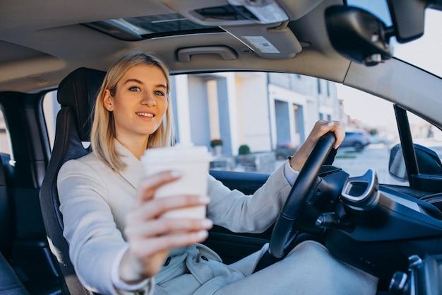 Femme assise à l'intérieur de la voiture électrique tout en chargeant une tasse de café Photo gratuit