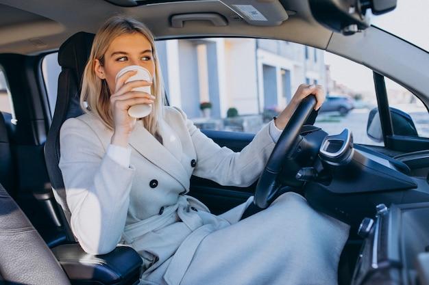 Femme assise à l'intérieur de la voiture électrique tout en chargeant avec une tasse de café Photo gratuit
