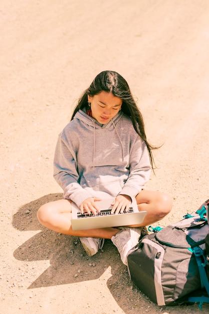 Femme assise avec les jambes croisées sur la route et travaillant sur un ordinateur portable Photo gratuit