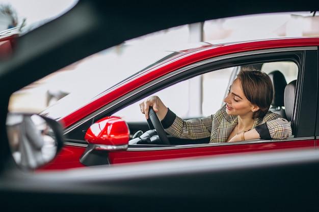 Femme assise je voiture dans un showrrom de voiture Photo gratuit