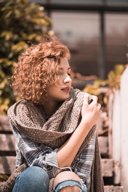 Femme assise sur les marches et tenant une écharpe Photo gratuit