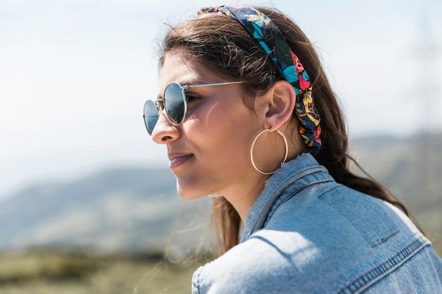 Femme assise sur la montagne et regardant au loin Photo gratuit