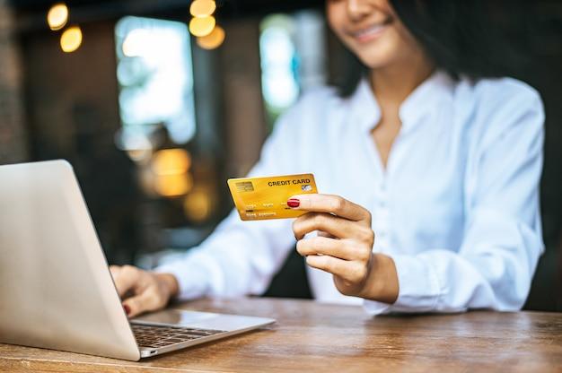 Femme assise avec un ordinateur portable et payée avec une carte de crédit dans un café Photo gratuit