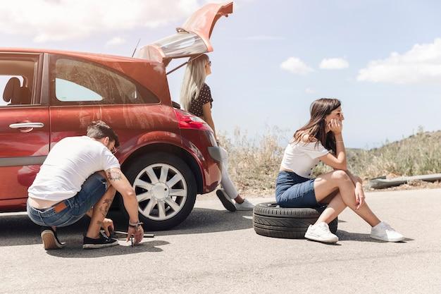 Femme assise sur un pneu près de l'homme, changer la roue de la voiture sur la route Photo gratuit