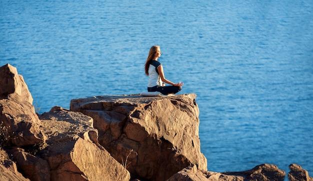 Femme assise en position de lotus sur un rocher au-dessus de la mer et méditant. yoga en plein air Photo Premium