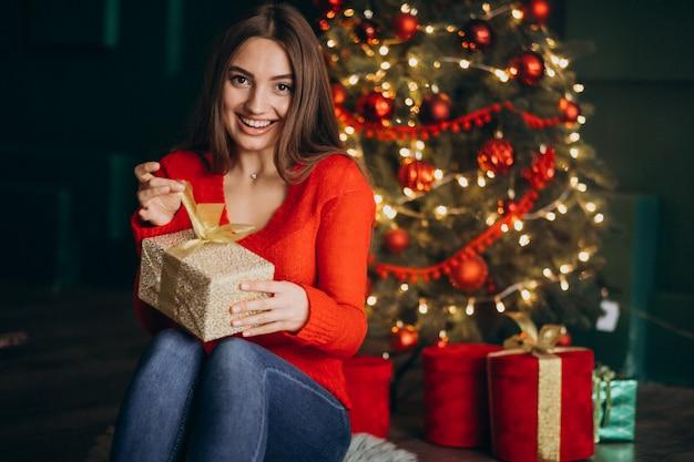 Femme assise près d'un arbre de noël et déballage du cadeau de noël Photo gratuit