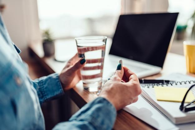 Femme assise près du bureau et prenant des médicaments Photo Premium