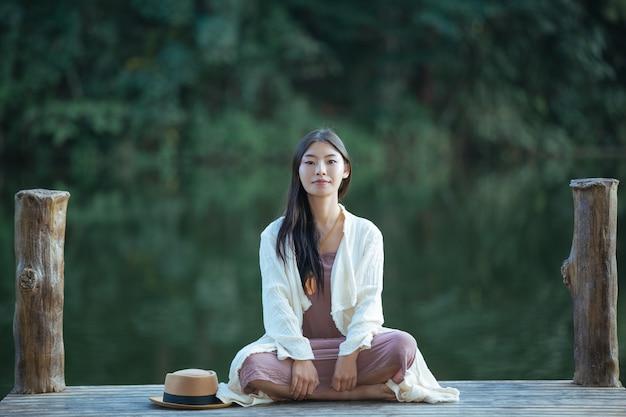 Femme assise sur le radeau au bord de l'eau Photo gratuit