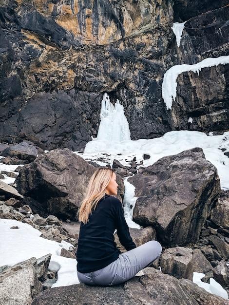 Femme assise sur les rochers Photo Premium