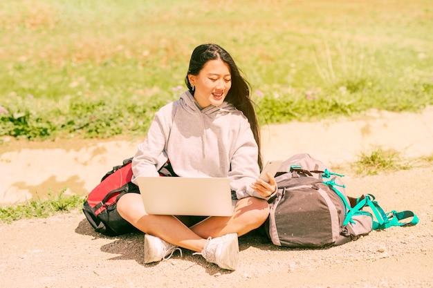 Femme assise sur la route en souriant et tenant un téléphone portable parmi les sacs à dos Photo gratuit