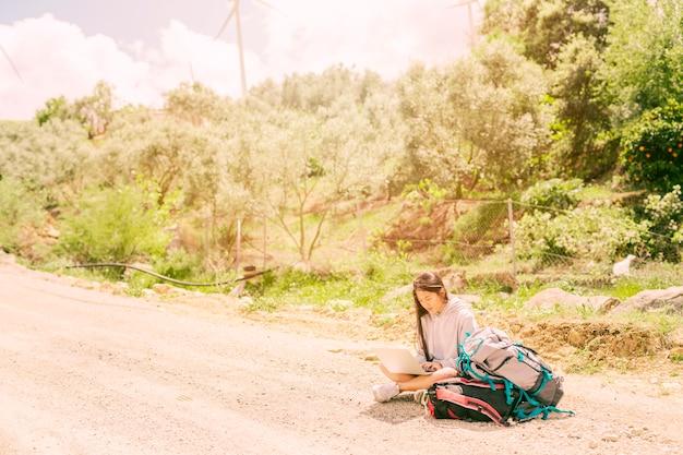Femme assise sur la route et en train de taper sur un cahier parmi des sacs à dos Photo gratuit