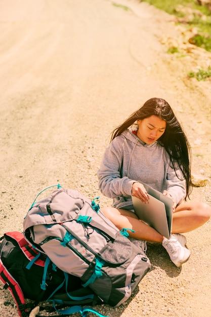 Femme assise sur la route et travaillant sur un ordinateur portable parmi des sacs à dos Photo gratuit