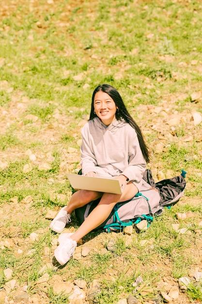 Femme assise sur un sac à dos avec ordinateur portable et regardant la caméra Photo gratuit