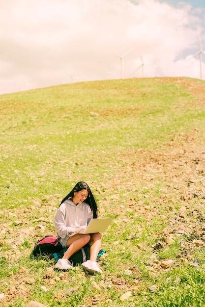 Femme assise sur un sac à dos et travaillant dans un ordinateur portable sur une colline verdoyante Photo gratuit