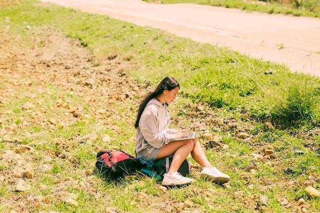 Femme assise sur un sac à dos et travaillant dans un ordinateur portable le long de la route Photo gratuit