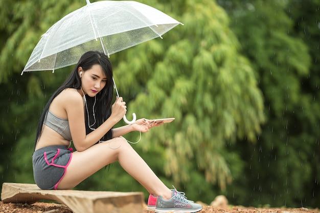 Femme assise seule avec parapluie. concept de prendre une pause Photo Premium