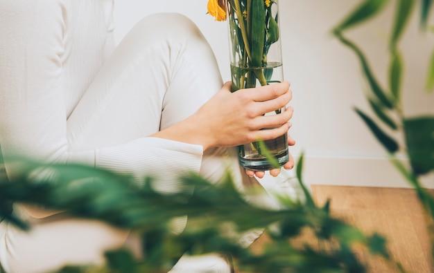 Femme assise sur le sol avec des fleurs dans un vase Photo gratuit