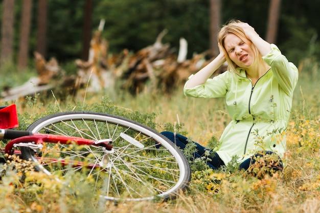 Femme assise sur le sol avec un mal de tête Photo gratuit